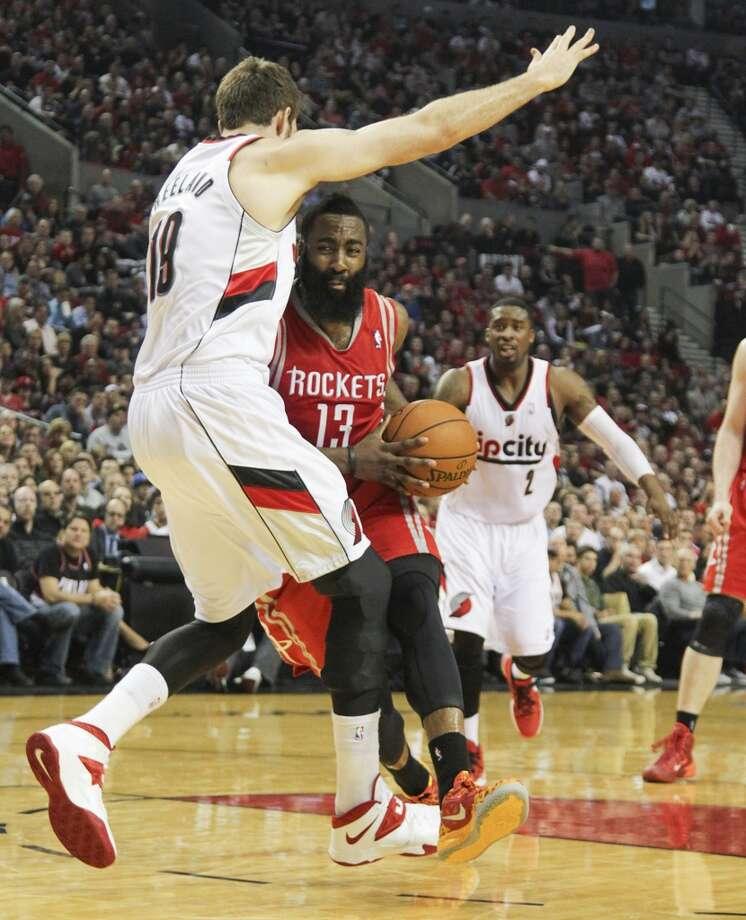 Rockets guard James Harden drives on Portland center Joel Freeland. Photo: James Nielsen, Houston Chronicle