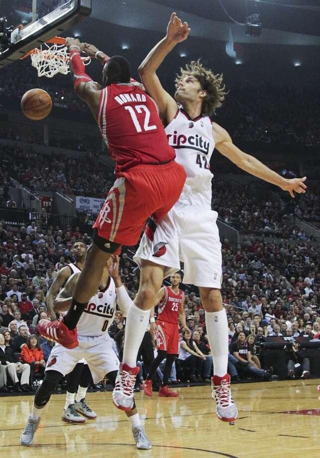 Rockets center Dwight Howard  dunks past Portland center Robin Lopez. Photo: James Nielsen, Houston Chronicle