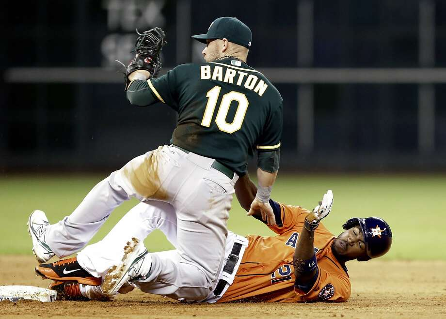 Oakland Athletics first baseman Daric Barton (10) knocks Houston Astros' Dexter Fowler (21) over whil trying to tag him out on a double to center field in the fourth inning of a baseball game on Friday, April 25, 2014, in Houston. (AP Photo/Pat Sullivan) Photo: Pat Sullivan, Associated Press