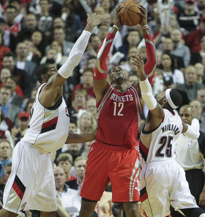 Rockets center Dwight Howard reaches for a rebound against Trail Blazers forward LaMarcus Aldridge and guard Mo Williams. Photo: James Nielsen, Houston Chronicle