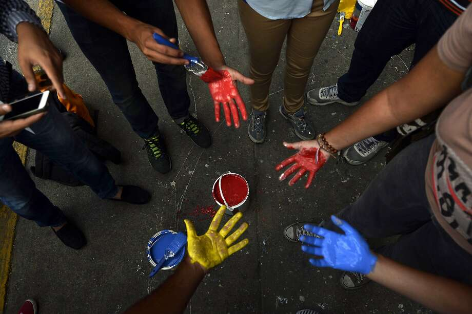 TOPSHOTS Students paint their hands to leave their prints on a wall as they protest against the government of Venezuelan President Nicolas Maduro, in Caracas, on April 25, 2014. Venezuela's government and opposition are holding talks to address the root causes of months of deadly protests which broke out in February and have left 41 dead and some 600 injured, as students and other angry Venezuelans denounce rampant crime, inflation, widespread shortages and other economic woes under President Maduro.  AFP PHOTO / JUAN BARRETOJUAN BARRETO/AFP/Getty Images Photo: Juan Barreto, AFP/Getty Images