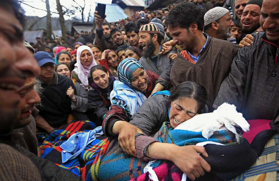 Sumaira Wani, wife of Zia-Ul-Haq mourns by the body of her husband during his funeral in Hirpora, some 65 kilometers (40 miles) north of Srinagar, India, Friday, April 25, 2014. Zia, an Indian poll official was killed soon after voting for the ongoing general elections, when suspected rebels fatally shot him and wounded four others in an attack on a bus in the Indian-controlled portion of Kashmir. (AP Photo/Dar Yasin) Photo: Dar Yasin, Associated Press