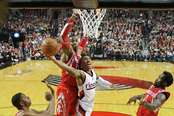 Portland guard Damian Lillard slices between the Rockets' Dwight Howard, Terrence Jones and Pat Beverley for two of his team-high 30 points in the first half.