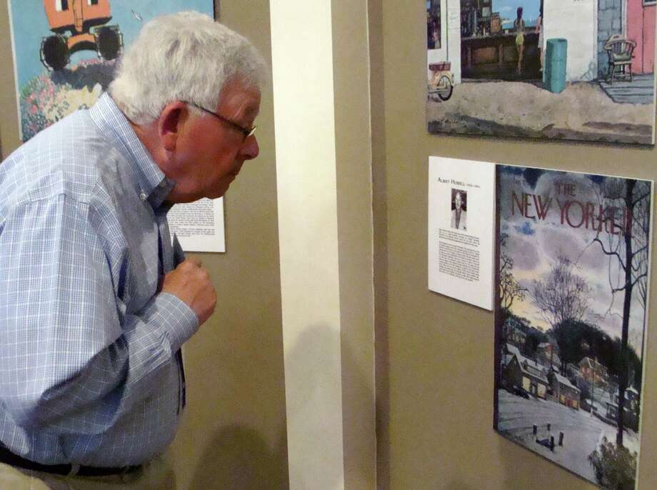 Tom Flatley of Fairfield leans in for a closer look at a reproduction of a New Yorker magazine cover by artist Albert Hubbell in an exhibit of New Yorker cover art at the Westport Historical Society. Photo: Meg Barone / Westport News