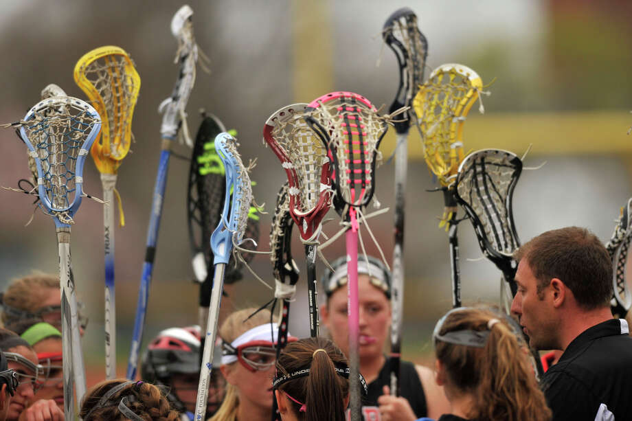 The Fairfield Warde girls lacrosse team hold their sticks up during a time out during their game against Stamford at Stamford High School in Stamford, Conn., on Tuesday, April 22, 2014. Fairfield Warde won, 12-6. Photo: Jason Rearick / Stamford Advocate