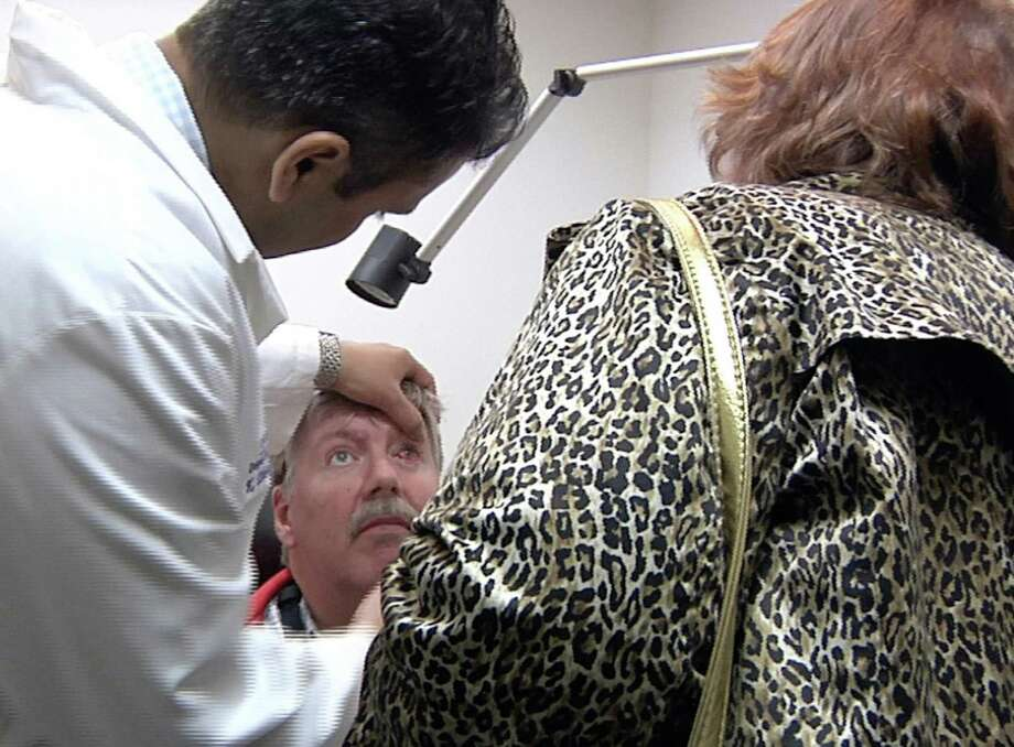 Earlier this month, Dr. Thiran Jayasundera checks the implant in Roger Pontz's left eye as his wife, Terri Pontz, looks on. Almost blind for years, the former factory worker can now recognize his cat and catch glimpses of his grandson. Photo: Mike Householder, STF / AP