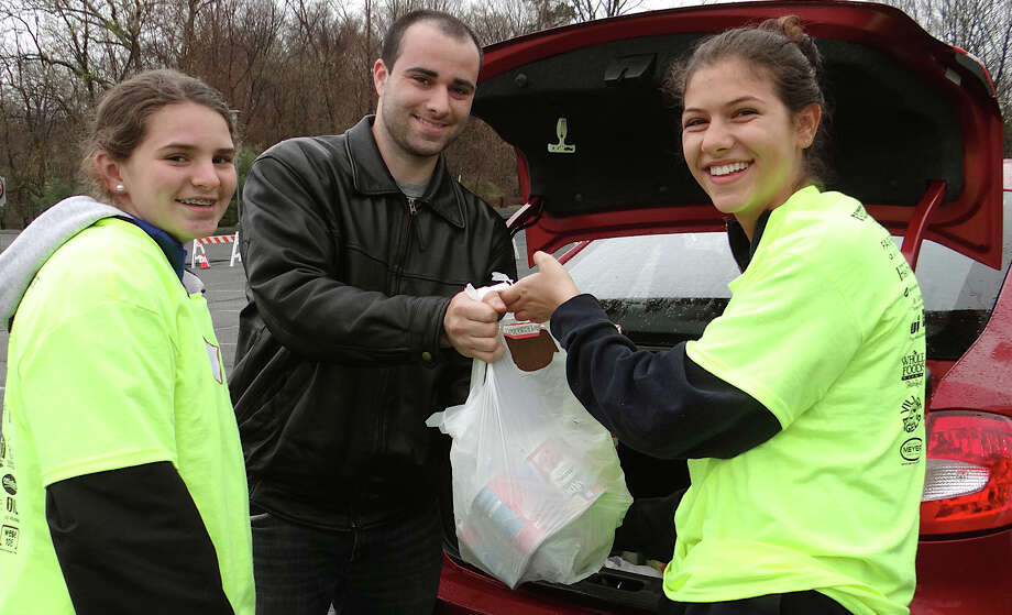 Joe Giffune handed a food donation to volunteers Sydney Burr and Caroline Ketcher on Saturday, the opening day of Fairfield's Townwide Food Drive at Fairfield Ludlowe High School. Photo: Mike Lauterborn / Fairfield Citizen