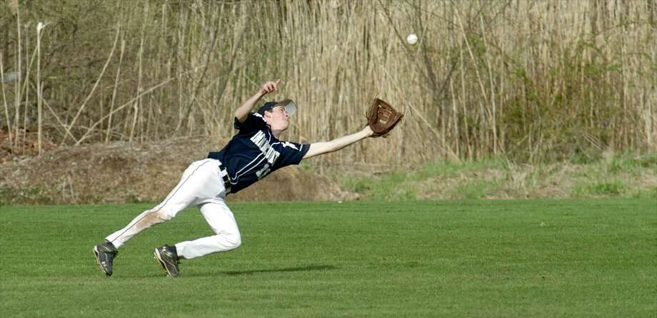 Immaculate's Shane Murphy, #11, reaches for a fly ball during the SWC boys baseball game between Newtown High School and Immaculate High School, in Danbury, Conn, on Friday, April 25, 2014. Photo: H John Voorhees III / The News-Times Freelance