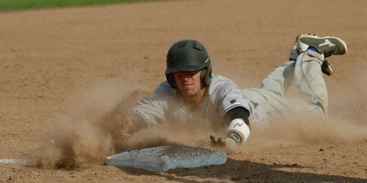 Newtown's Virgil Procacinni, #5, slide safely into third on a wild pitch during the SWC boys baseball game between Newtown High School and Immaculate High School, in Danbury, Conn, on Friday, April 25, 2014.