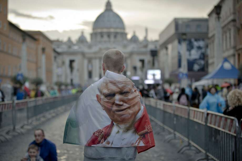 A man wears a banner with an image of Pope John Paul II outside St. Peter's Square at the Vatican. Photo: Vadim Ghirda, Associated Press