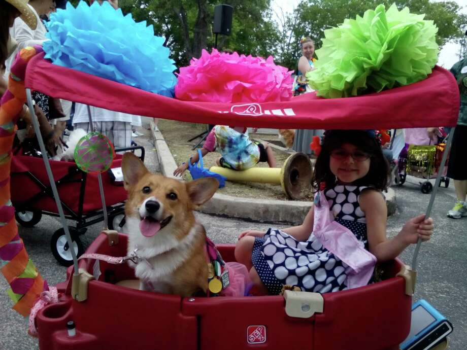 Gianna Ozuniga, 4, and Searci, 1, enjoy the Fiesta Pooch Parade on Saturday at the Alamo Heights pool. Photo: Edmond Ortiz / San Antonio Expre