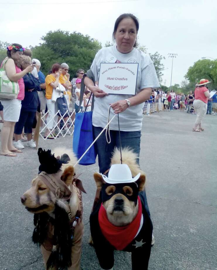 Jolene, 3, dressed as Tonto (left) and Elvira, 8, as the Lone Ranger, won Most Creative during the Fiesta Pooch Parade costume contest Saturday at the Alamo Heights pool. Joyce Hayes (standing) is their owner. Photo: Edmond Ortiz / San Antonio Expre