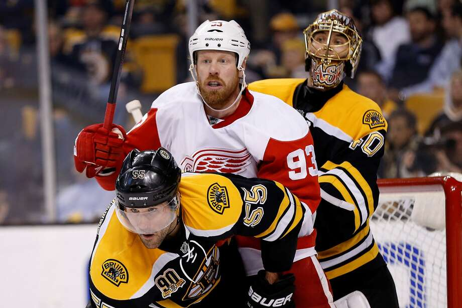 Bruins goalie Tuukka Rask (rear) peaks around Red Wings right wing Johan Franzen and Boston defenseman Johnny Boychuk in Game 5. Photo: Greg M. Cooper, Reuters