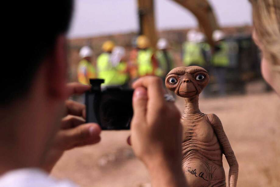 A man takes a photo of an E.T. doll in Alamogordo, N.M, Saturday, April 26, 2014. Producers of a documentary dug in an southeastern New Mexico landfill in search of millions of cartridges of the Atari 'E.T. the Extra-Terrestrial' game that has been called the worst game in the history of video gaming and were buried there in 1983. (AP Photo/Juan Carlos Llorca) Photo: Juan Carlos Llorca, STF / AP