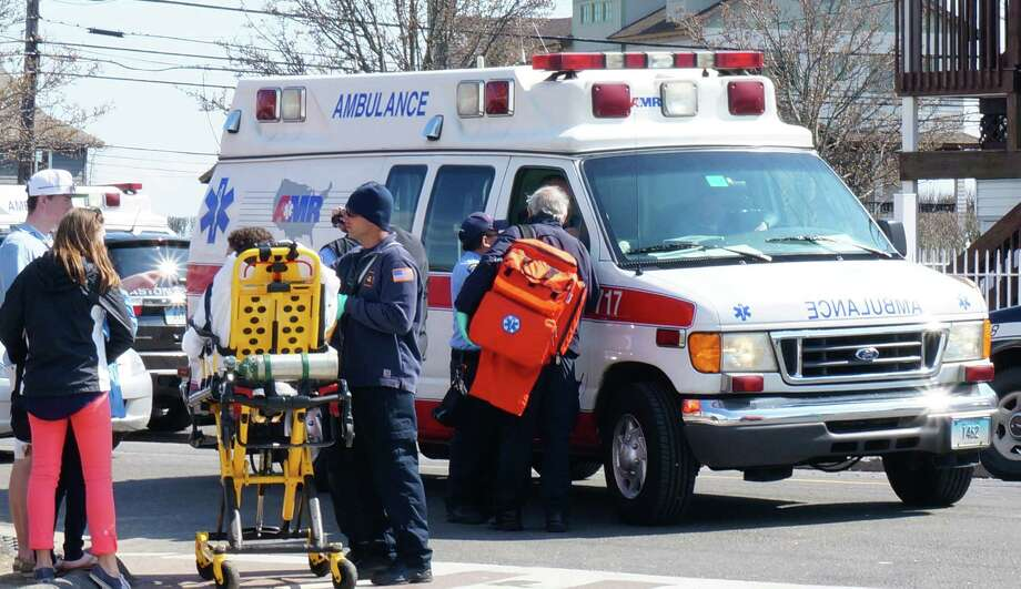 An ambulance at the scene of one of several calls Saturday afternoon during the Clam Jam student party at Fairfield Beach. Photo: Genevieve Reilly / Fairfield Citizen