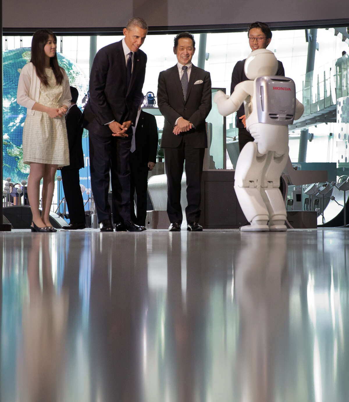 """**EDS: RETRANSMISSION TO PROVDE ALTERNATIVE CROP** President Barack Obama watches a robot made by Honda, named ASIMO, perform during a tour of the National Museum of Emerging Science and Innovation in Tokyo, April 24, 2014. Obama said he found the several robots he saw demonstrations from during the tour """"a little scary"""" and """"too life-like."""" (Stephen Crowley/The New York Times)"""