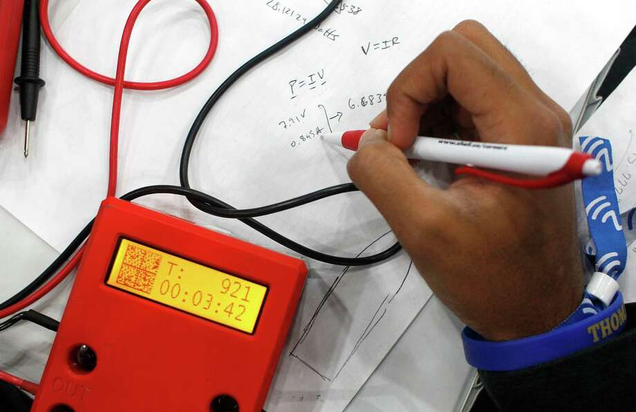 Akshay Jaggi, 17, a junior at St. John's School in Houston uses an equation to attempt to solve a power issue his team was having. Photo: Johnny Hanson, Houston Chronicle / © 2014  Houston Chronicle