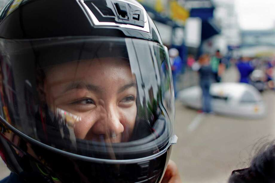 Westside High School senior, Sarah Wong, 17, puts on her helmet before driving her team's battery electric vehicle outside the George R. Brown Convention Center during the Shell Eco-marathon Saturday, April 26, 2014, in Houston. Photo: Johnny Hanson, Houston Chronicle / © 2014  Houston Chronicle