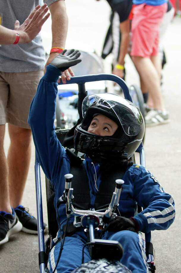Westside High School senior, Sarah Wong, 17, gets a high-five from a teammate before driving her team's battery electric vehicle outside the George R. Brown Convention Center. Photo: Johnny Hanson, Houston Chronicle / © 2014  Houston Chronicle