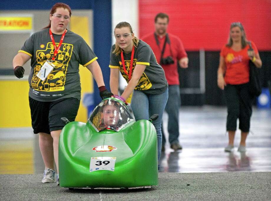 Granite Falls High School students from Granite Falls, Wash., Jocelyn Gimpel, left, and Katy Phillips push their driver, Kelsey Green out to the track during the Shell Eco-marathon at the George R. Brown Convention Center Saturday, April 26, 2014, in Houston. Photo: Johnny Hanson, Houston Chronicle / © 2014  Houston Chronicle