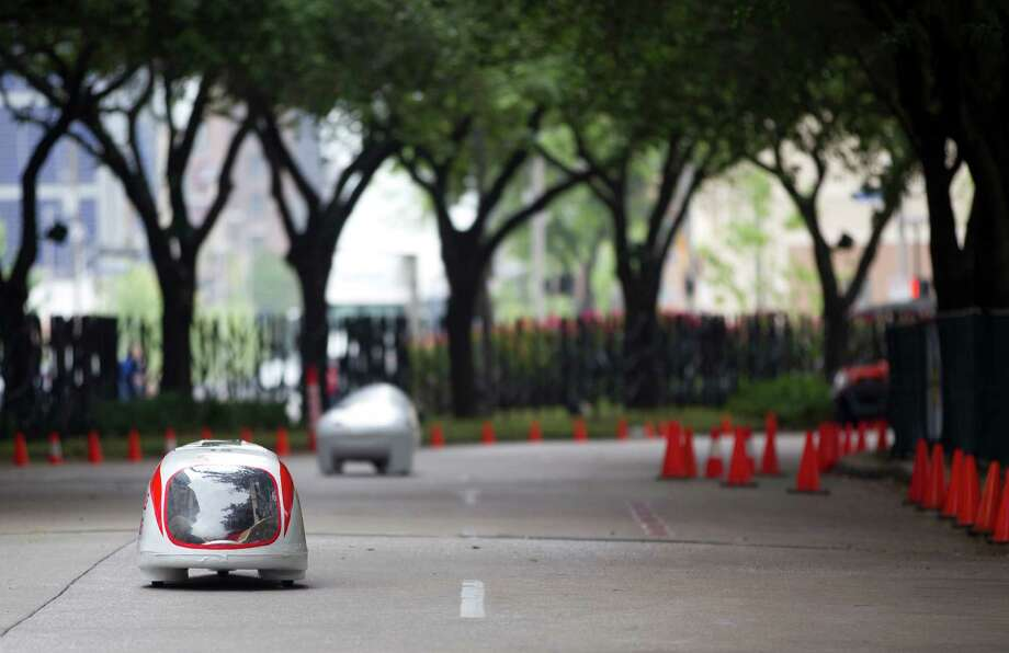 Two vehicles make their way around the Discovery Green track during the Shell Eco-marathon at the George R. Brown Convention Center Saturday, April 26, 2014, in Houston. Photo: Johnny Hanson, Houston Chronicle / © 2014  Houston Chronicle
