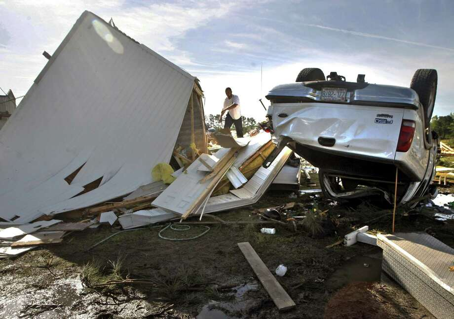 A man salvages belongings from an overturned mobile home in Greenville, N.C.,  on Saturday. Officials said multiple tornadoes damaged more than 200 homes and spent up to 10 minutes on the ground Friday. Photo: Aileen Devlin, MBO / The Daily Reflector