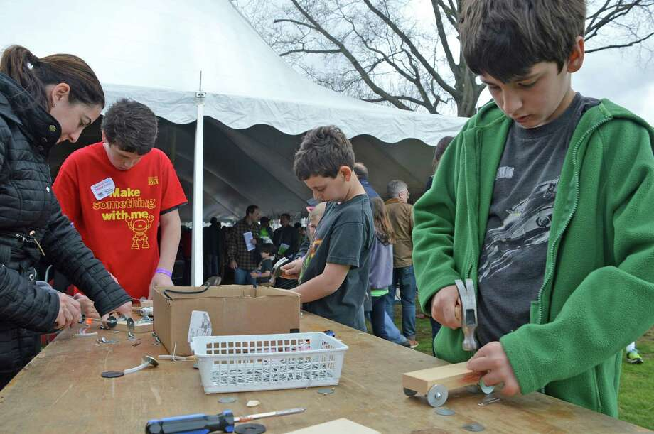 A group sets to making things the old-fashioned way -- using hammers -- at the Mini Maker Faire on Saturday at the Westport Library. Photo: Jarret Liotta / Fairfield Citizen