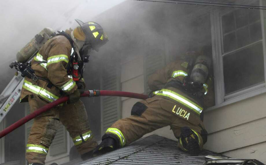 Firefighters work at the scene of a fire on Summit Ridge Road the morning of Saturday, April 26, 2014. Photo: Jon Tenca/PuckStopperPhoto.com, Contributed Photo / Stamford Advocate Contributed