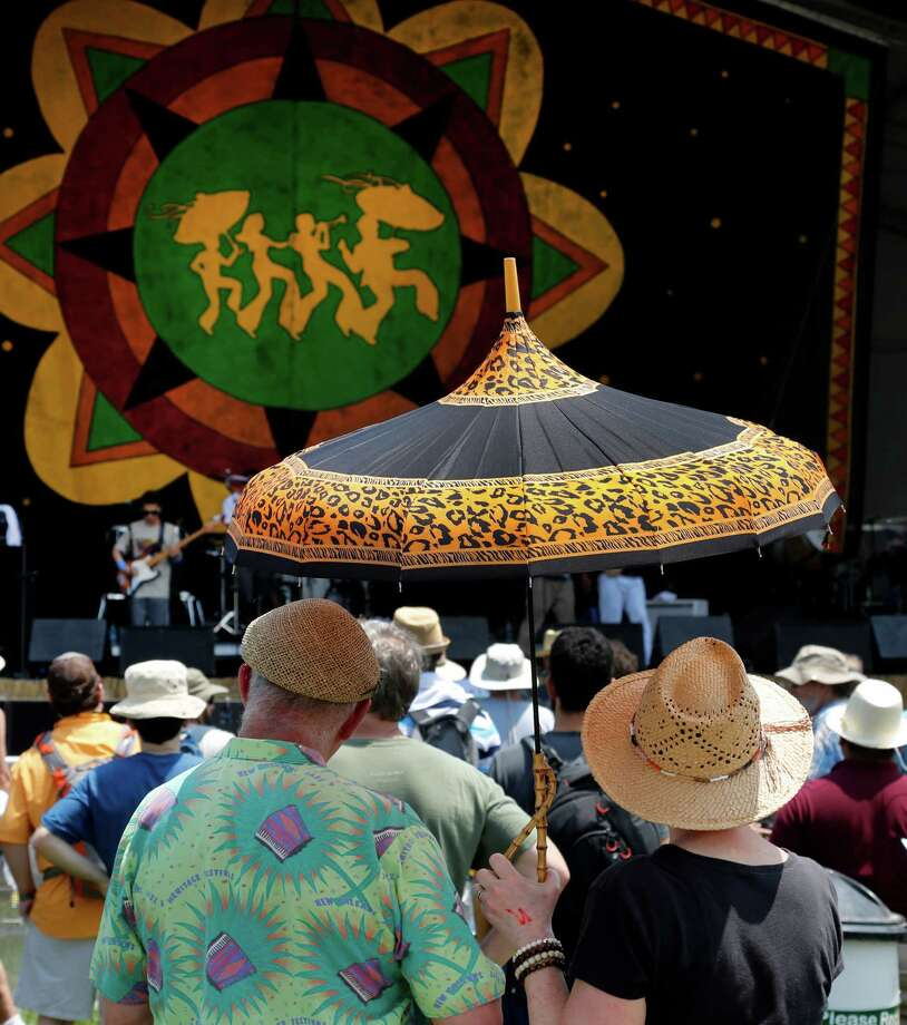 Alice and Bruce Mitchell, left, of Nashville, find shade under their shared umbrella while listening to the music of Baiana System of Brazil at Congo Square at the New Orleans Jazz and Heritage Festival in New Orleans, Friday, April 25, 2014. The sights and sounds of Brazil are being featured as part of festival's tribute to countries that have contributed to New Orleans' culture. Photo: Doug Parker, Associated Press / FR 170928AP