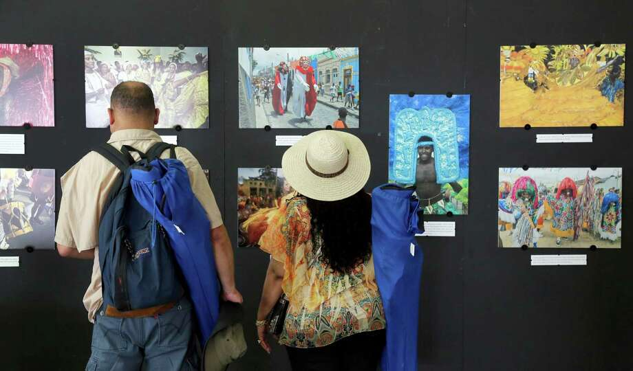 Jazz Fest visitors view art at the Caso do Brasil tent at the New Orleans Jazz and Heritage Festival in New Orleans, Friday, April 25, 2014. The sights and sounds of Brazil are being featured as part of festival's tribute to countries that have contributed to New Orleans' culture. ( Photo: Doug Parker, Associated Press / FR 170928AP