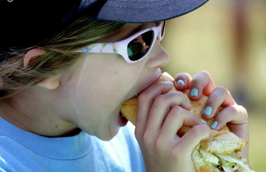 Elizabeth Johnston, 9, of New Orleans, chows down on a Cochon de Lait sandwich at the New Orleans Jazz and Heritage Festival in New Orleans, Friday, April 25, 2014. This is Elizabeth's 9th Jazz Fest, including when her mother went into labor with her nine years ago while at the fest. Photo: Doug Parker, Associated Press / FR 170928AP