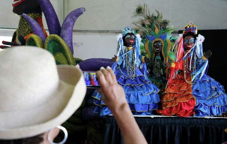 A Jazz Fest visitor takes a photo of the puppetry by Fernando Augusto Goncalves, from Olinda, Brazil, at the New Orleans Jazz and Heritage Festival in New Orleans, Friday, April 25, 2014. The sights and sounds of Brazil are being featured as part of festival's tribute to countries that have contributed to New Orleans' culture. Photo: Doug Parker, Associated Press / FR 170928AP