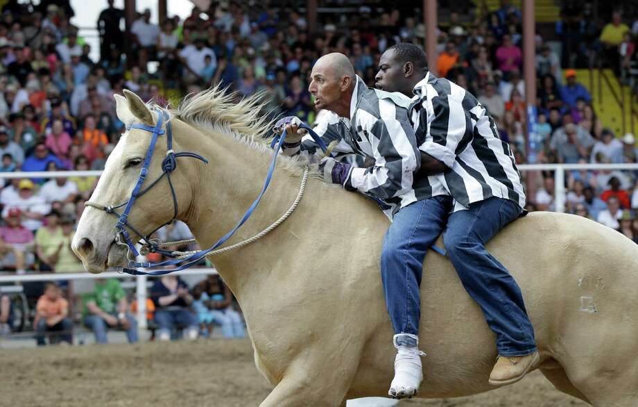 Inmates gallop in the Buddy Pick-Up event at the Angola Prison Rodeo on Saturday. Photo: Gerald Herbert, STF / AP