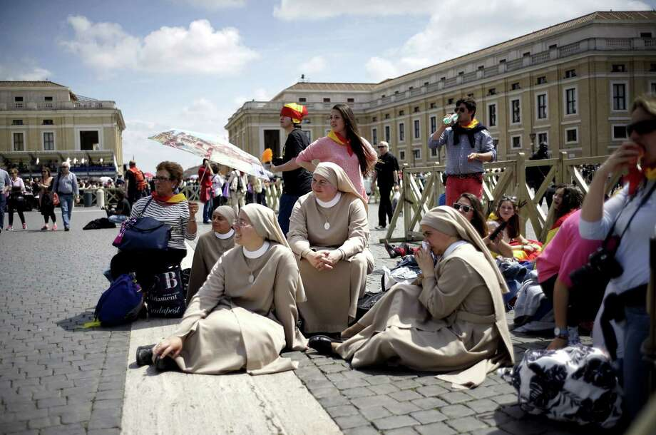 Nuns and other pilgrims from Mexico sit in St. Peter's Square at the Vatican, gathering to attend Sunday's ceremony in which John XXIII and John Paul II will be elevated to sainthood. Photo: Andrew Medichini / Associated Press / AP