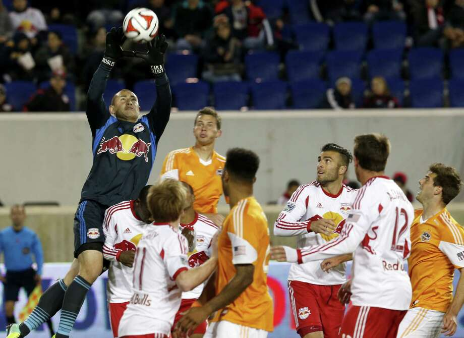Red Bulls keeper Luis Robles, left, intercepts a Dynamo threat Wednesday in New York's 4-0 win. The loss extended the Orange's winless streak to five. Photo: Julio Cortez, STF / AP
