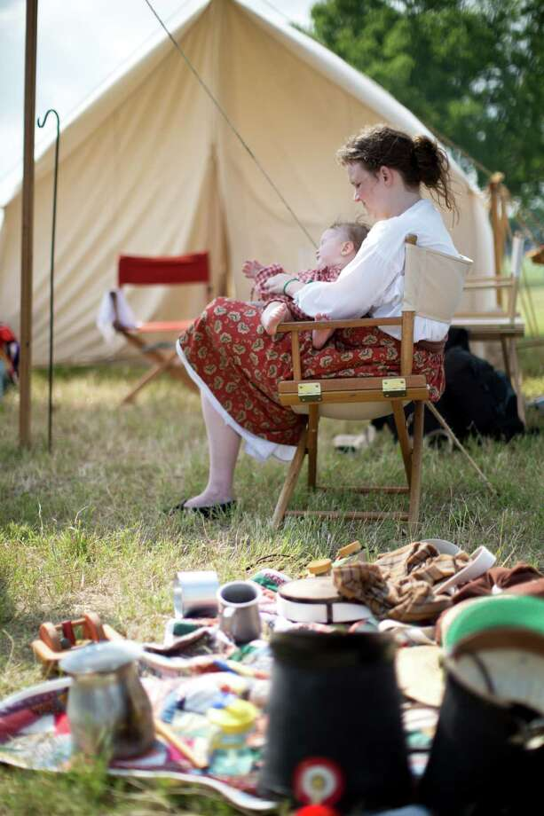 Amanda Maloney takes care of her baby boy Davin Maloney while dressed with clothing appropriate of the 19th century during the re-enactment of the Battle of San Jacinto, Saturday, April 26, 2014, in La Porte. Photo: Marie D. De Jesus, Houston Chronicle / © 2014 Houston Chronicle
