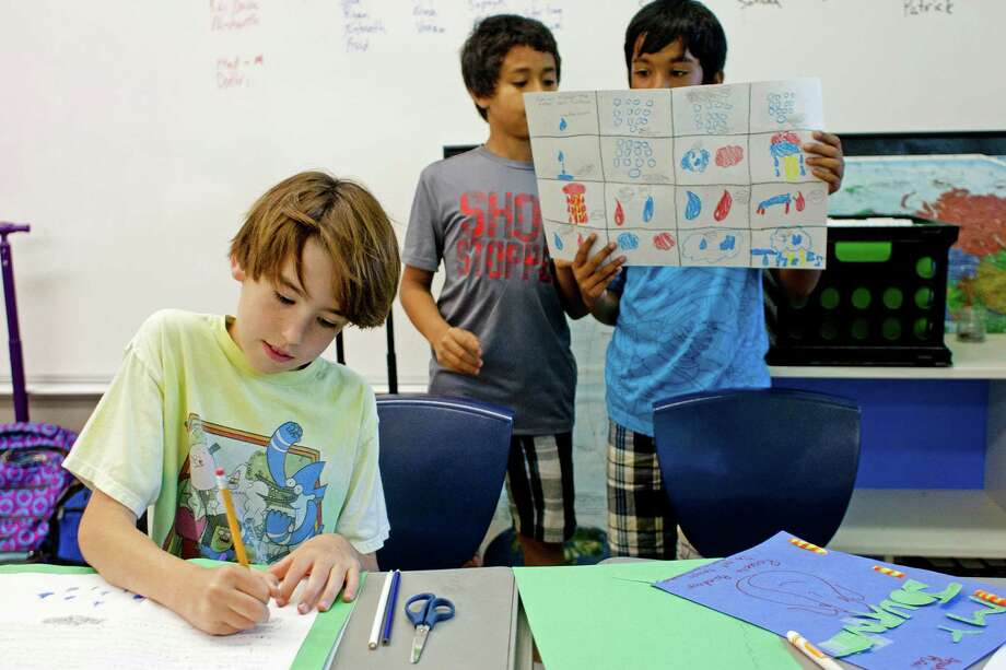 "Fourth-graders, from left, Kai Davis, Shaun Waller and Ryan Rosario work on their science project about ""being a drop of rain"" at the T.H. Rogers School in April 2014. The school is an HISD magnet campus for gifted students. Photo: Johnny Hanson, Houston Chronicle / © 2014  Houston Chronicle"