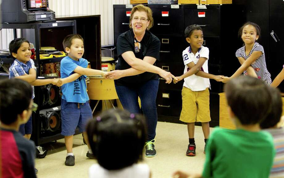 "Music teacher, Jan Harasim, and a kindergarten class sing and use sign language to the song ""What a Wonderful World"" at T. H. Rogers School in April 2014. T.H. Rogers is a popular HISD magnet school for gifted students. Photo: Johnny Hanson, Houston Chronicle / © 2014  Houston Chronicle"