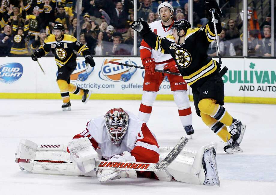 Detroit Red Wings' Jonas Gustavsson (50) sprawls on the ice as Boston Bruins' Torey Krug, center, celebrates a goal by teammate Zdeno Chara during the second period in Game 5 in the first round of the NHL hockey Stanley Cup playoffs  in Boston, Saturday, April 26, 2014. (AP Photo/Michael Dwyer) ORG XMIT: MAMD112 Photo: Michael Dwyer / AP