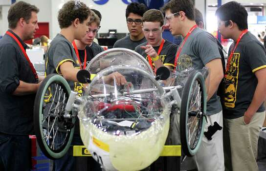 The team from St. John's School in Houston uses an equation to attempt to solve a power issue his team was having with the amount of power the vehicle received from its solar panels during the Shell Eco-marathon at the George R. Brown Convention Center on Saturday. Photo: Johnny Hanson / © 2014  Houston Chronicle