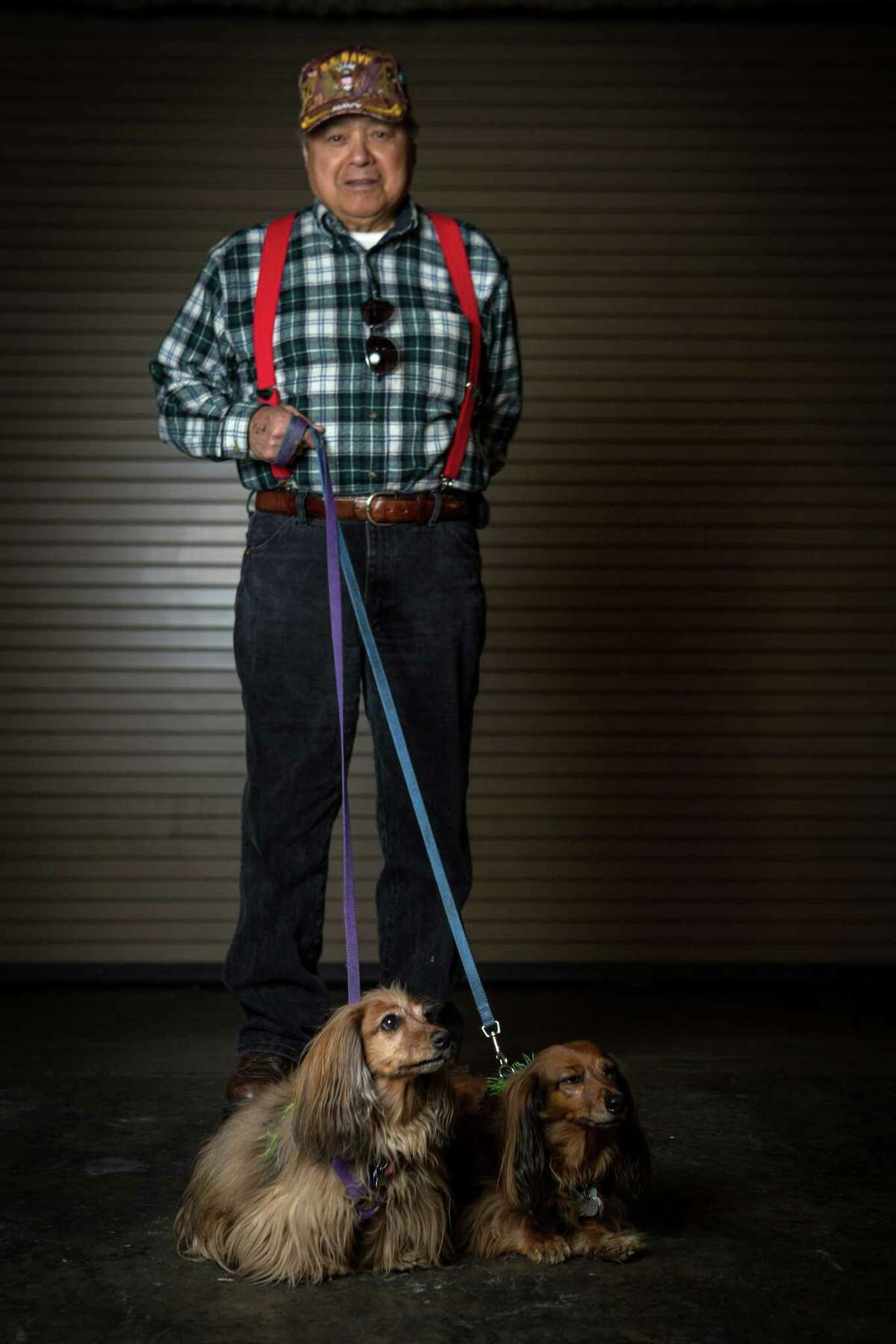 Suni and Cher, longhair dachshunds, are shown with owner Mark Sison of the Nisqually Tribe.