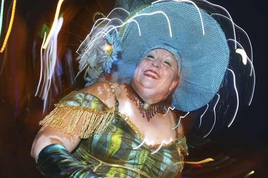 Margaret Cisneros dances with Destino Danzzar Performance Group during the Fiesta Flambeau Night Parade in downtown San Antonio  on April 26, 2014. Photo: Tom Reel, San Antonio Express-News