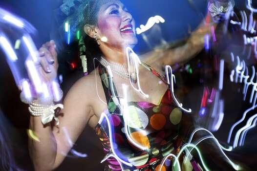 Matia Elena Weisser dances with Las Charangas during the Fiesta Flambeau Night Parade in downtown San Antonio  on April 26, 2014. Photo: Tom Reel, San Antonio Express-News