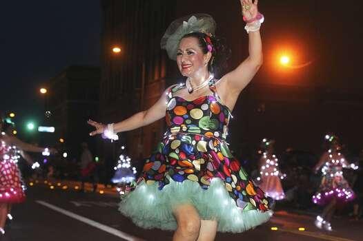 Maria Elena Weissner dances with Las Charangas during the Fiesta Flambeau Night Parade in downtown San Antonio  on April 26, 2014. Photo: Tom Reel, San Antonio Express-News