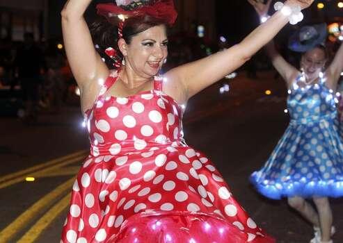 Lisa Castaneda dances on Broadway with Las Charangas during the Fiesta Flambeau Night Parade in downtown San Antonio  on April 26, 2014. Photo: Tom Reel, San Antonio Express-News