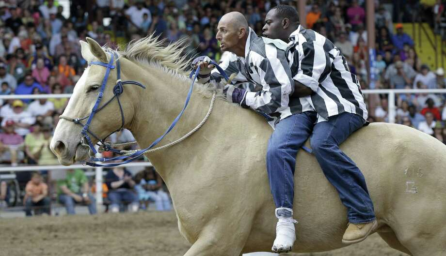 Inmates ride a horse in the Buddy Pick-Up event at the Angola Prison Rodeo in Angola, La. Photo: Gerald Herbert / Associated Press / AP