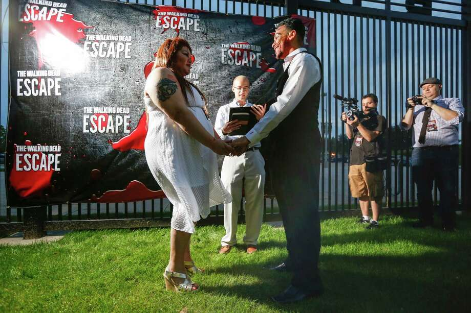 Participants run for their lives from zombies April 26, 2014 in Houston at the Walking Dead Escape at Reliant Stadium. Also Cassie Charlene Hernandez and Andrew Ellis Nieves tie the knot in a zombie wedding. Photo: Eric Kayne, For The Chronicle / Eric Kayne