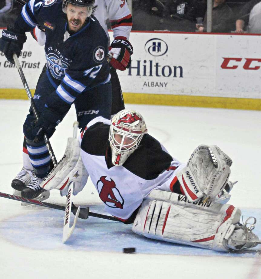 St. John's IceCaps' #42 Josh Lunden left, looks on as Albany Devils's goalie Keith Kincaid makes a save during the second game of a best-of-5 American Hockey League playoff series at the Times Union Center Saturday April 26, 2014, in Albany, NY.  (John Carl D'Annibale / Times Union) Photo: John Carl D'Annibale / 00026569A