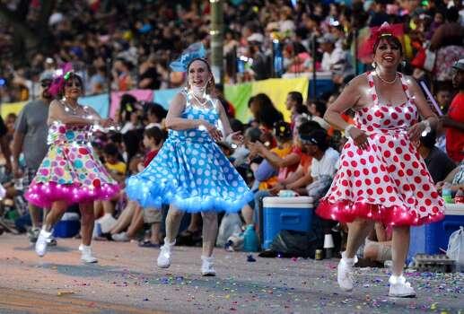 Members of the Charanga's de San Antonio dance along Broadway during the Fiesta Flambeau parade on Saturday, April 26, 2014. Photo: Billy Calzada, San Antonio Express-News