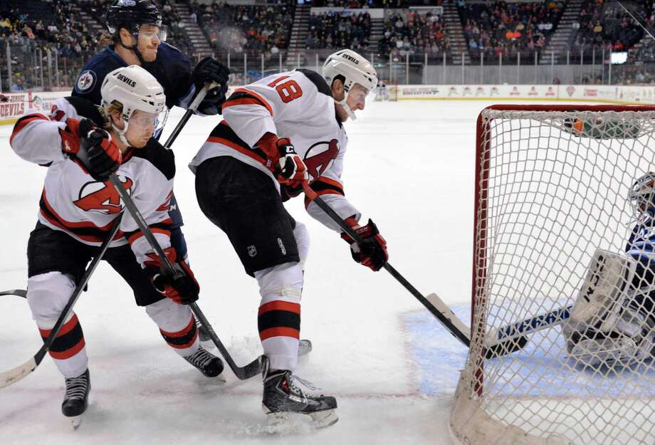 Albany Devils' #18 Stefan Matteau, center, scores against St. John's IceCaps goalie Michael Hutchinson, right, during the second game of a best-of-5 American Hockey League playoff series at the Times Union Center Saturday April 26, 2014, in Albany, NY. At left is Devil's # 21 Mattias Tedenby.   (John Carl D'Annibale / Times Union) Photo: John Carl D'Annibale / 00026569A